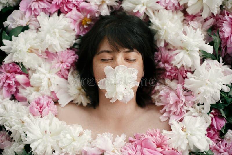 Portret die van bohovrouw met witte pioen in mond in roze pioenen liggen Creatieve kunst bloemenfoto Aroma en kuuroordconcept stock foto's