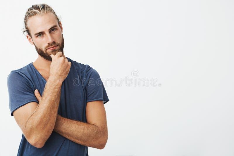 Portret die van de aantrekkelijke jonge mens met de modieuze hand van de kapselholding op kin met nadenkende uitdrukking, binnen  royalty-vrije stock afbeelding