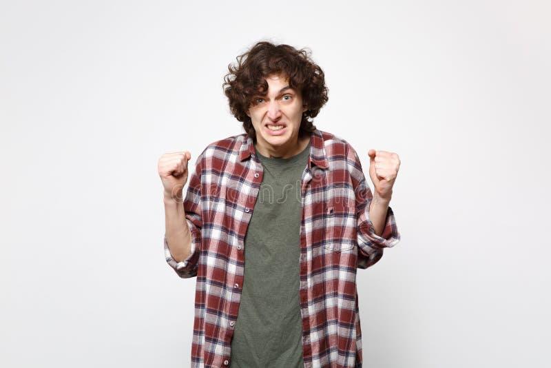 Portret die van die de boze geïrriteerde jonge mens die in vrijetijdskleding camera, vuisten dichtklemmen kijken op witte muur wo stock fotografie
