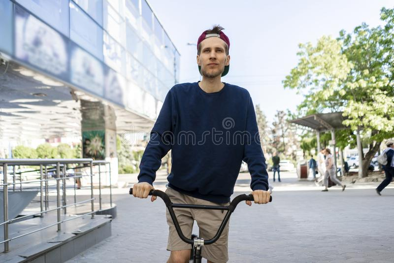 Portret die van de cheereful jonge mens op de fiets, in de stadsstraten berijden royalty-vrije stock foto