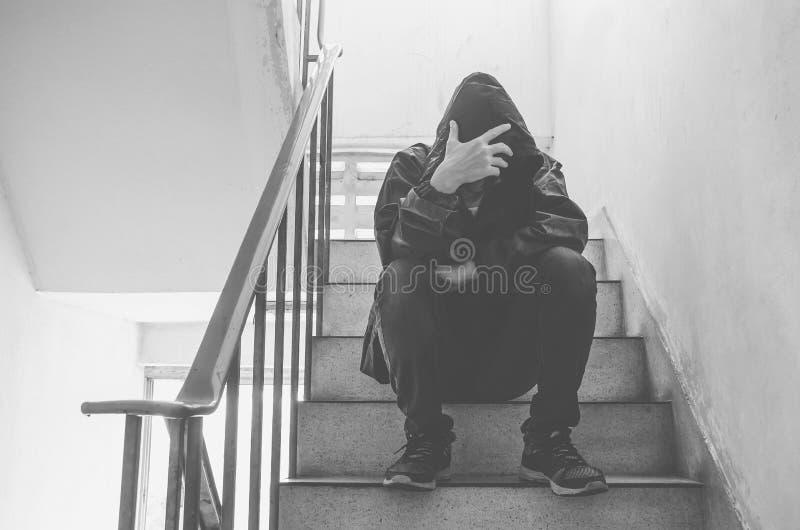 Portret die van de droevige jonge mens zijn gezicht behandelen met handen die op oude treden zitten stock afbeelding