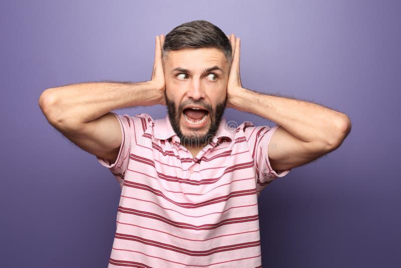 Portret die van de emotionele mens oren behandelen met handen op kleurenachtergrond royalty-vrije stock foto