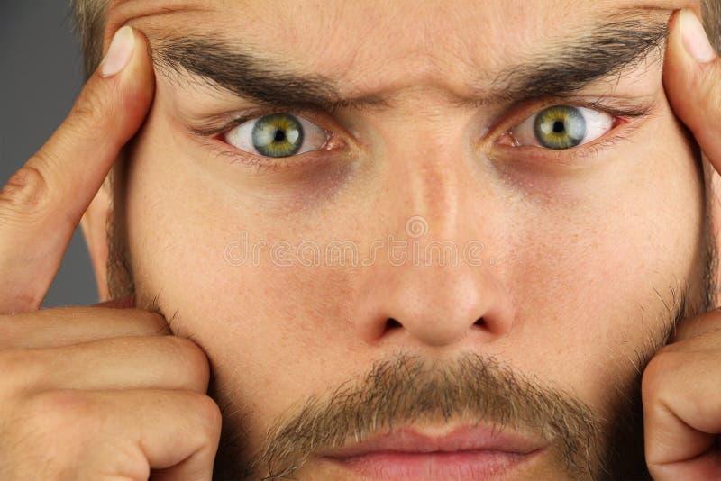 Portret die van de geconcentreerde mens, de huid op het gezicht tighting die - tempels wrijven, verandert de vorm van de ogen, cl royalty-vrije stock foto's