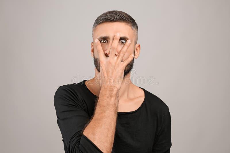 Portret die van de gekke mens gezicht behandelen met hand op grijze achtergrond stock foto