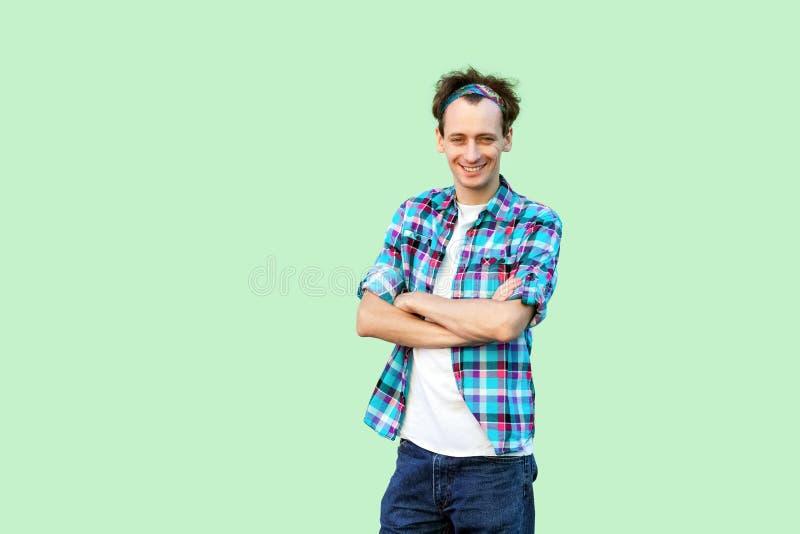 Portret die van de gelukkige tevreden jonge mens in toevallig blauw geruit overhemd en hoofdband die, camera het bekijken met cro stock foto's