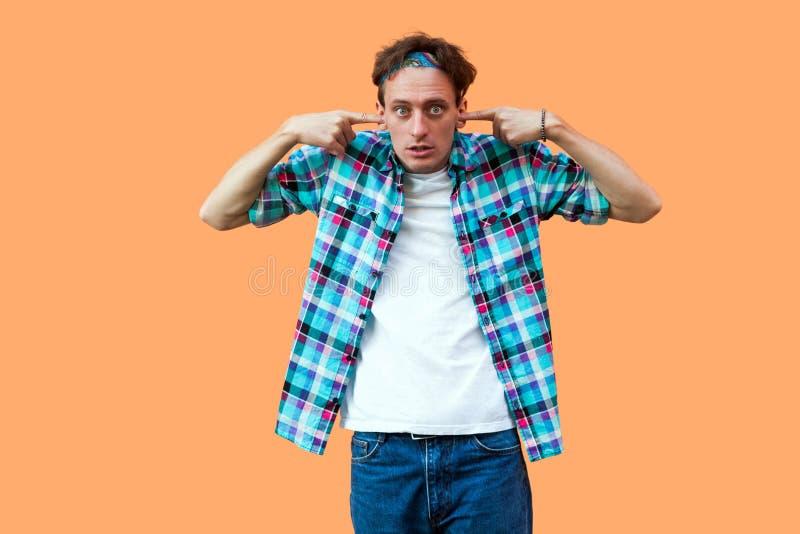 Portret die van de geschokte of verwarde jonge mens in toevallig blauw geruit overhemd en hoofdband die, vinger op zijn oren zett stock afbeelding