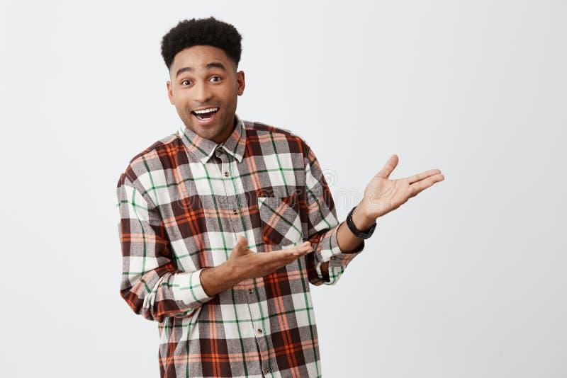 Portret die van de grappige jonge donker-gevilde mooie mens die met afrokapsel in toevallig overhemd, witte achtergrond tonen gli stock foto's