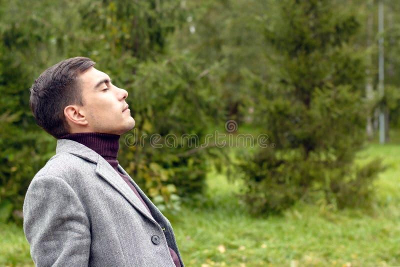 Portret die van de jonge aantrekkelijke mens met een grijze laag, in de verse de herfstlucht ademen in het Park, die zijn gezicht royalty-vrije stock foto's