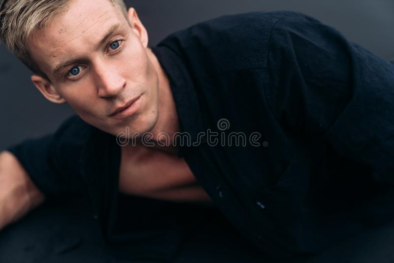 Portret die van de knappe blauw-eyed mens in zwart overhemd op zwart zandstrand liggen stock foto's