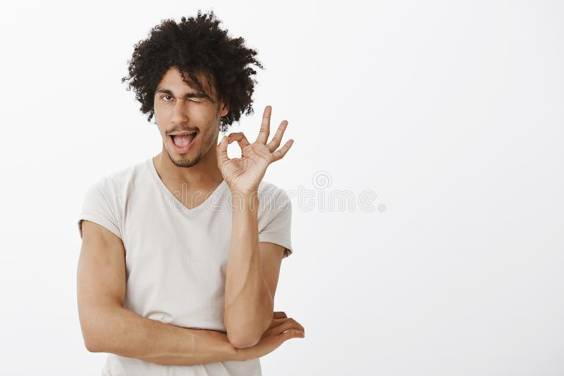 Portret die van de knappe flirty en gelukkige Spaanse mens met afro haicut, o.k. of o.k. gebaar tonen, en van wat houden knipogen stock foto
