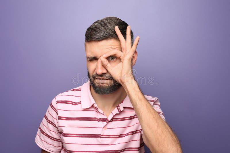Portret die van de mens O.K. gebaar op kleurenachtergrond tonen stock foto's