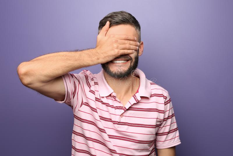 Portret die van de mens ogen behandelen met hand op kleurenachtergrond stock foto's