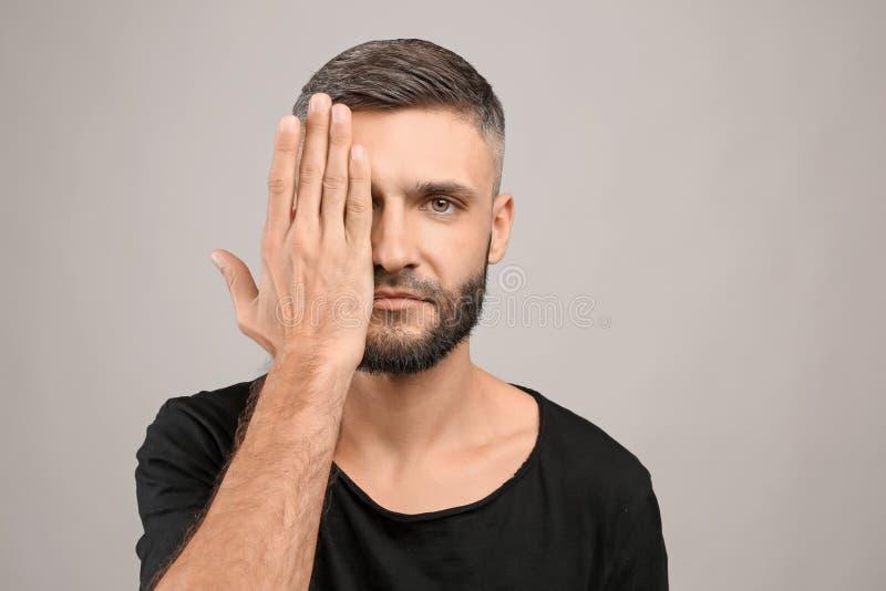 Portret die van de mens oog behandelen met hand op grijze achtergrond royalty-vrije stock afbeeldingen