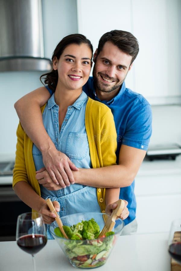 Portret die van de mens vrouw in de keuken omhelzen royalty-vrije stock afbeelding