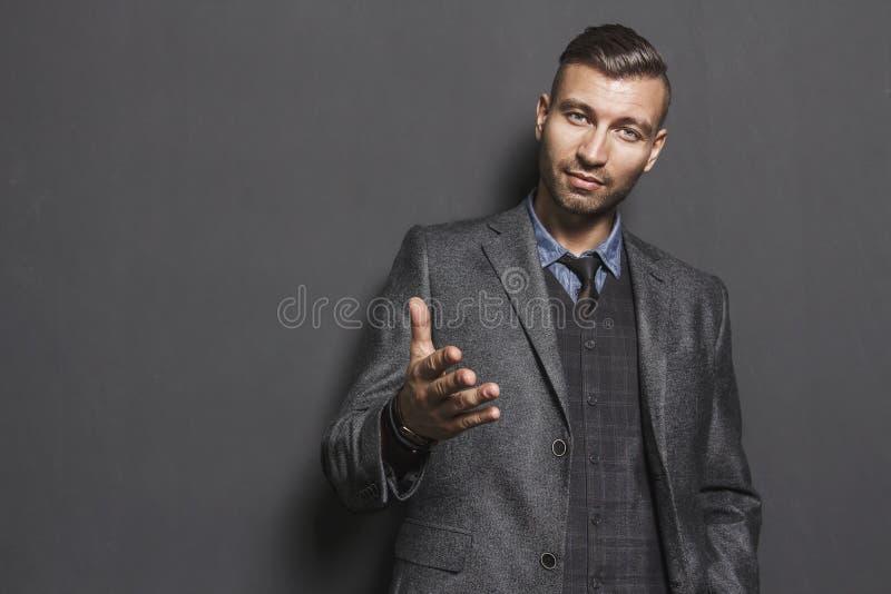 Portret die van de modieuze knappe mens uit zijn hand uitrekken zeker kijk van de modieuze succesvolle mens in grijs kostuum royalty-vrije stock afbeeldingen