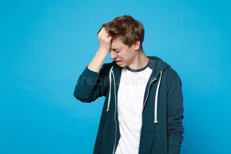 Portret die van die de schreeuwende gefrustreerde jonge mens in vrijetijdskleding met verminderd hoofd, hand op hoofd zetten op b stock foto