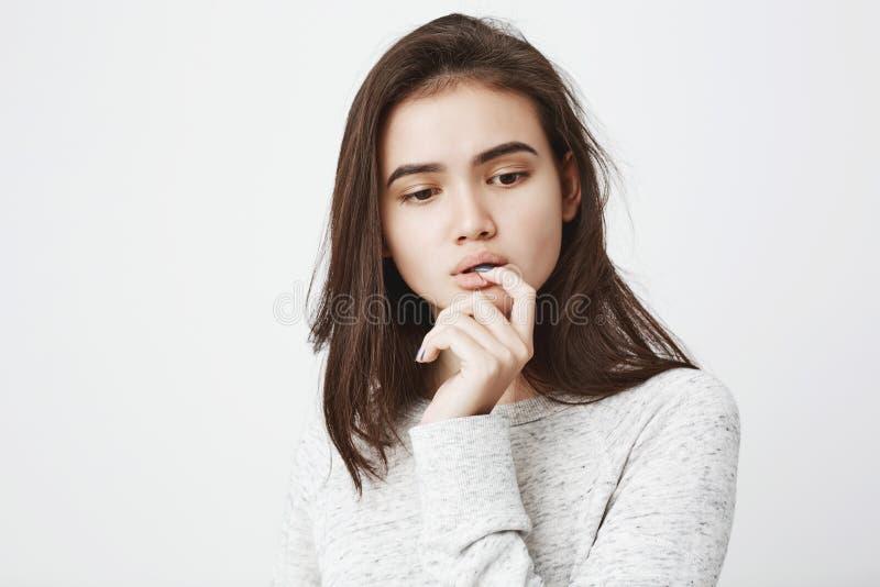 Portret die van dromerig teder meisje met nadenkende uitdrukking, hand houden dichtbij mond terwijl het bijten van vinger en neer stock foto's