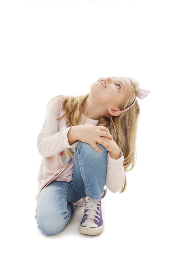 Portret die van een aanbiddelijke meisjezitting op de knieën, omhoog op copyspace kijken stock afbeelding