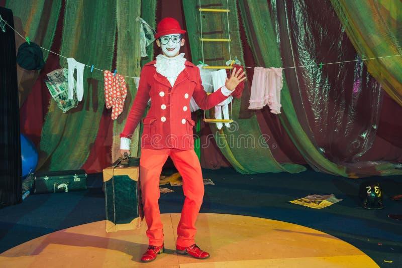 Portret die van een clown in een rode kostuum en een hoed, zijn hand golven stock foto's