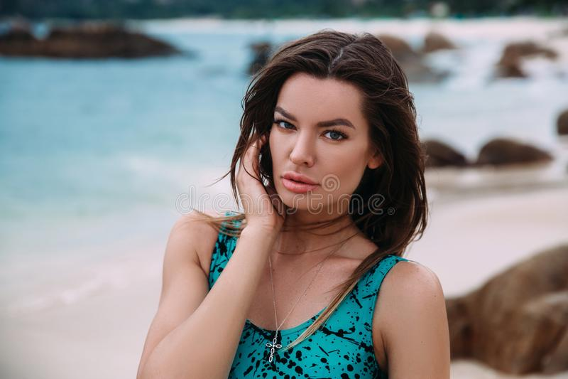 Portret die van een donker-haired mooie vrouw, op het strand het rusten, de wind ontwikkelt haar lang haar, het concept rust royalty-vrije stock fotografie