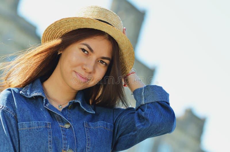 Portret die van een gelukkig vrolijk meisje in een de zomerhoed, in één hand zijn hoed, op de achtergrond van de Universiteit hou royalty-vrije stock afbeeldingen