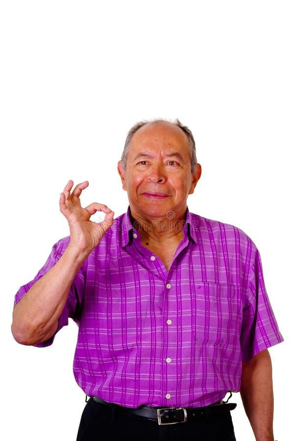 Portret die van een gelukkige oude mens, een succesvol teken met zijn hand doen en een purpere vierkante t-shirt in een wit drage royalty-vrije stock afbeeldingen
