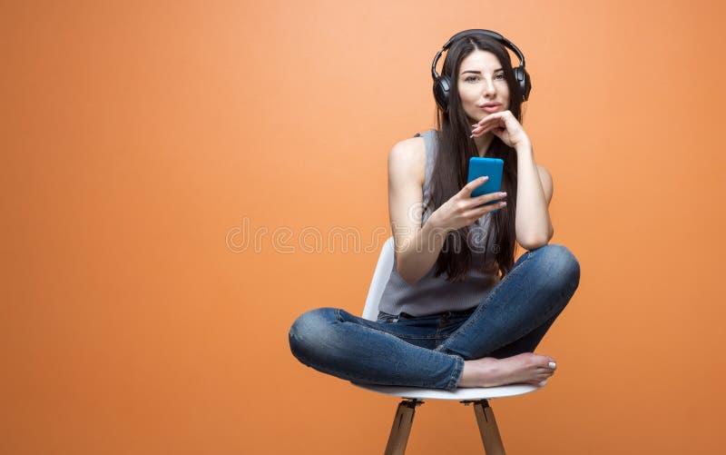 Portret die van een jong mooi meisje die aan muziek door de hoofdtelefoon en met een slimme telefoon in haar hoofd luisteren, als stock foto