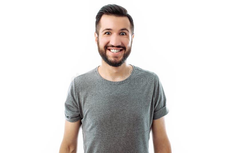 Portret die van een jonge mens met een baard, het grijze overhemd stellen voor de camera met een grote glimlach op een witte acht royalty-vrije stock afbeeldingen