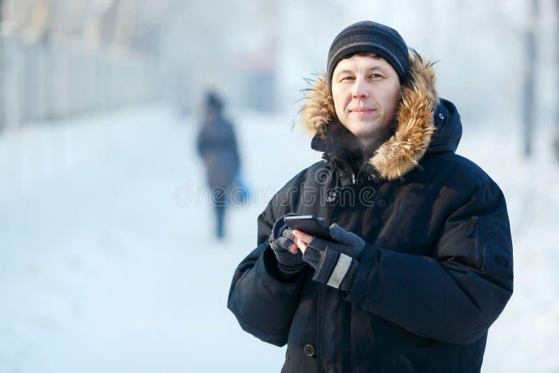 Portret die van een jonge Siberische mens met telefoon in handen, warm benedenjasje, bontkap dragen Koude de winterdag stock foto's