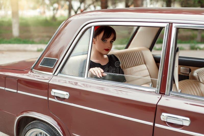 Portret die van een Kaukasisch mooi jong meisje in een zwarte uitstekende kleding, in de cabine van een uitstekende auto stellen stock foto
