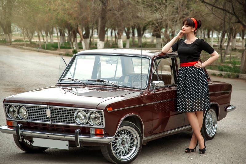 Portret die van een Kaukasisch mooi jong meisje in een zwarte uitstekende kleding, dichtbij een uitstekende auto stellen stock afbeeldingen