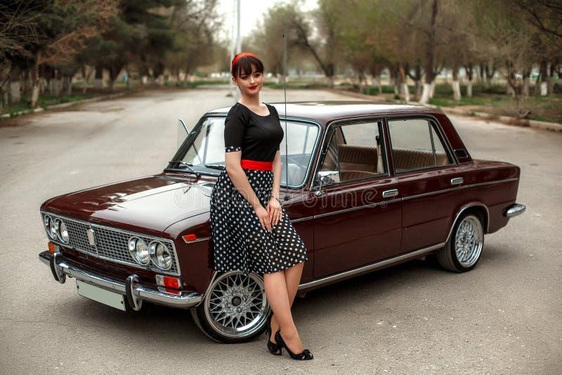 Portret die van een Kaukasisch mooi jong meisje in een zwarte uitstekende kleding, dichtbij een uitstekende auto stellen stock fotografie