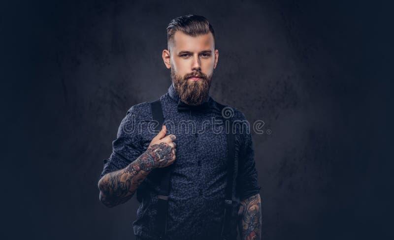 Portret die van een knappe ouderwetse hipster in een blauw overhemd en bretels, in een studio stellen stock afbeelding
