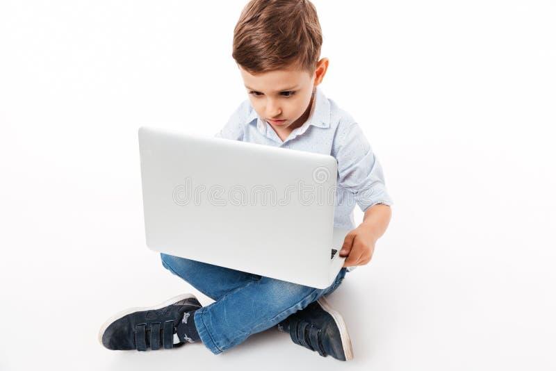 Portret die van een leuk klein jong geitje laptop computer met behulp van stock foto