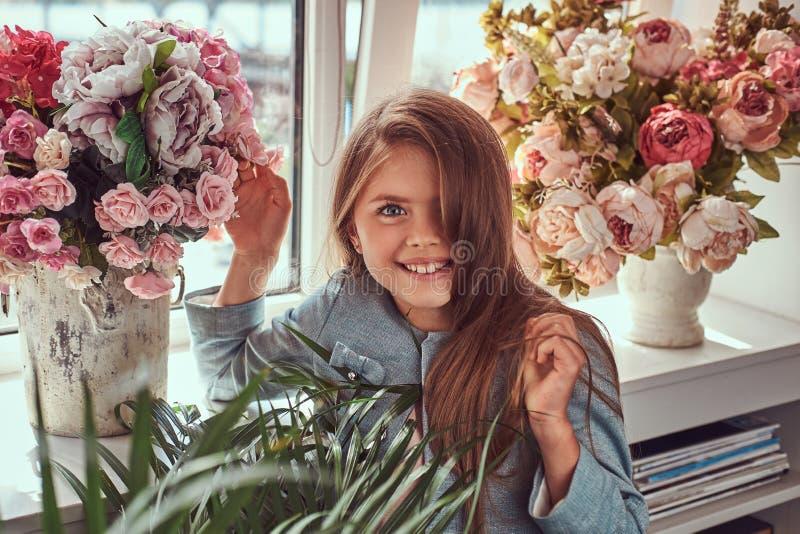 Portret die van een leuk meisje die met lange bruine haar en het doordringen blik een modieuze kleding dragen, met bloemen stelle stock fotografie