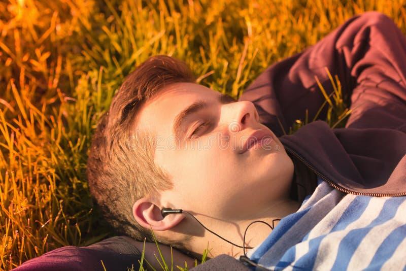 Portret die van een leuke tienerjongen die aan muziek luisteren, op een vers groen grasgebied liggen stock fotografie