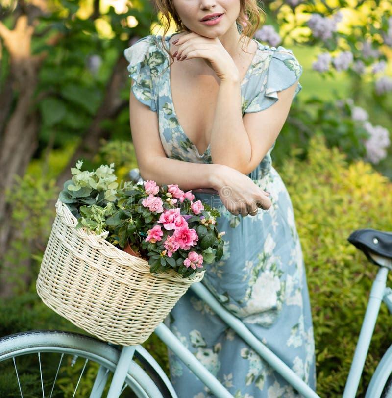 Portret die van een mooi meisje in het bos, een fiets met een mand van bloemen houden, achter de stralen van de zon, gebloeid bla royalty-vrije stock fotografie