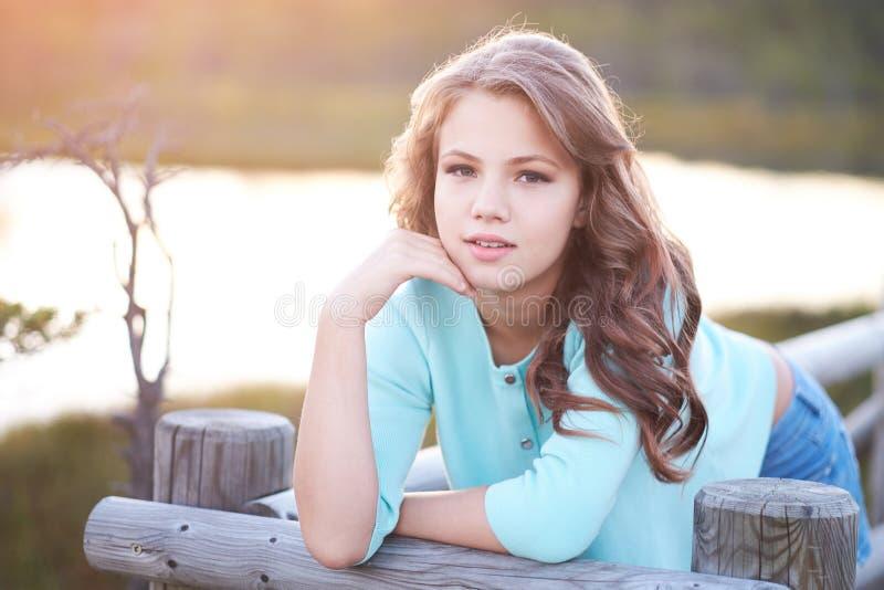 Portret die van een mooi meisje, zich in openlucht terwijl het leunen op een houten omheining bevinden stock afbeelding