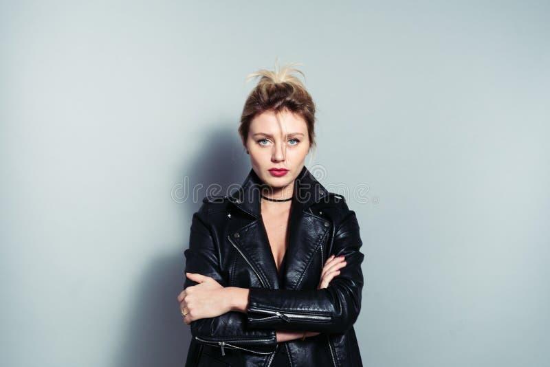 Portret die van een mooie blondevrouw, zwart fietserjasje dragen royalty-vrije stock foto