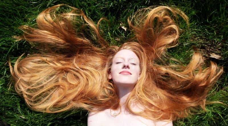 Portret die van een mooie jonge sexy roodharige vrouw, in de de lentezon liggen, die op het groene gras, het rode gedrapeerde haa royalty-vrije stock fotografie