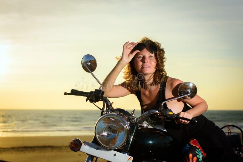 Portret die van een mooie vrouwenzitting op motorfiets, en zonnebril op het voorhoofd glimlachen houden royalty-vrije stock fotografie