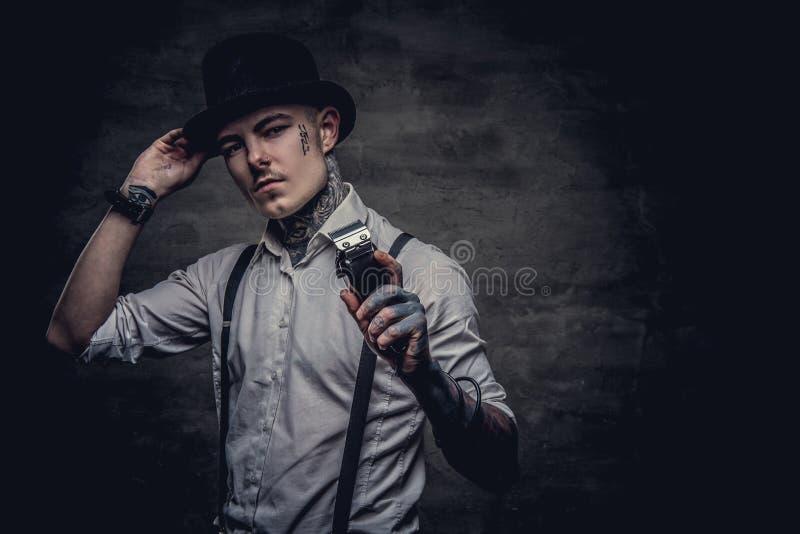 Portret die van een ouderwetse getatoeeerde kapper die een wit overhemd met bretels en cilinderhoed dragen, a bekijken royalty-vrije stock foto