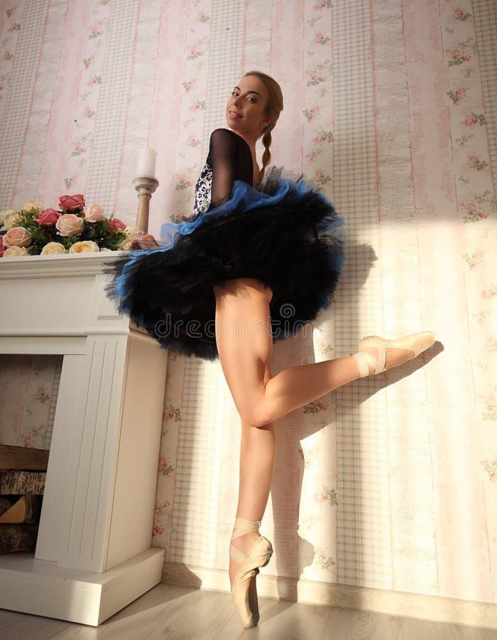 Portret die van een professionele balletdanser in zonlicht in huisbinnenland, zich op één been bevinden royalty-vrije stock foto