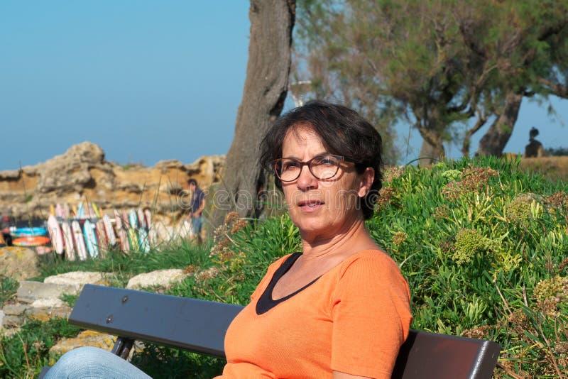 Portret die van een rijpe vrouw met oogglazen, op een bank zitten royalty-vrije stock fotografie