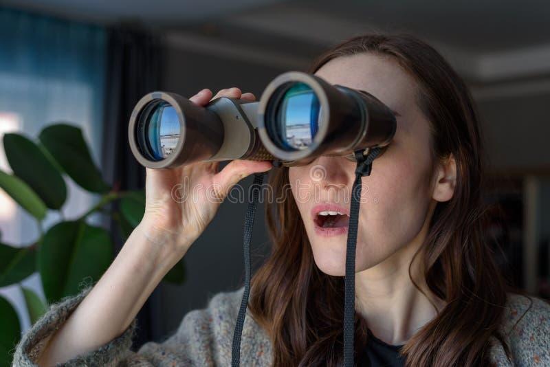 Portret die van een verrast brunette met verrekijkers die uit het venster, op buren spioneren kijken royalty-vrije stock foto