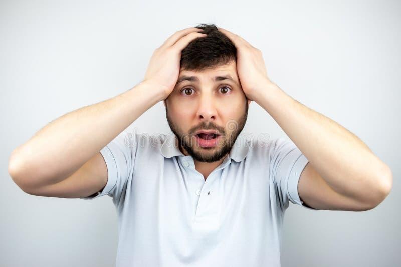 Portret die van een verraste gebaarde mens met ogen en wijd open mond, zijn hoofd met zijn handen, op een wit houden stock afbeeldingen