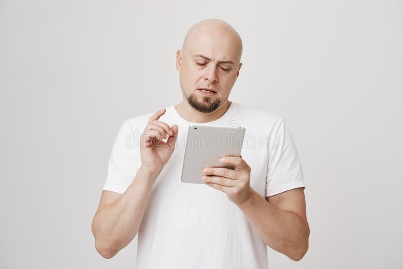 Portret die van ernstig bezig kaal Europees mannetje met baardholding tablet en het typen van iets, zich over grijs bevinden stock afbeelding