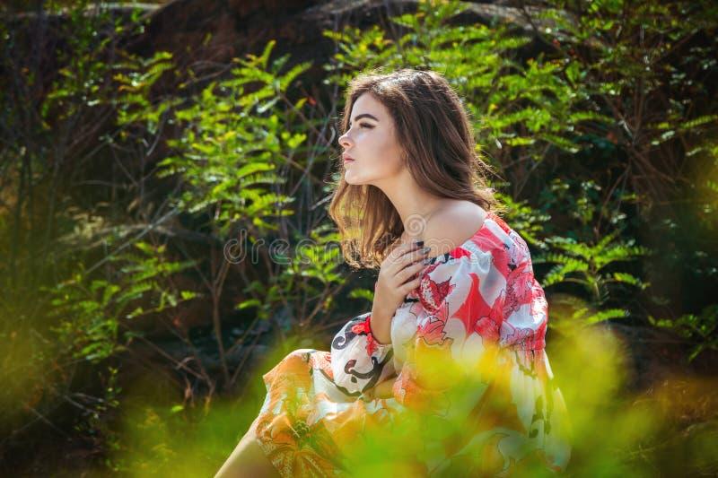 Portret die van ernstige donkerbruine jonge vrouw, in een bos zitten royalty-vrije stock foto's