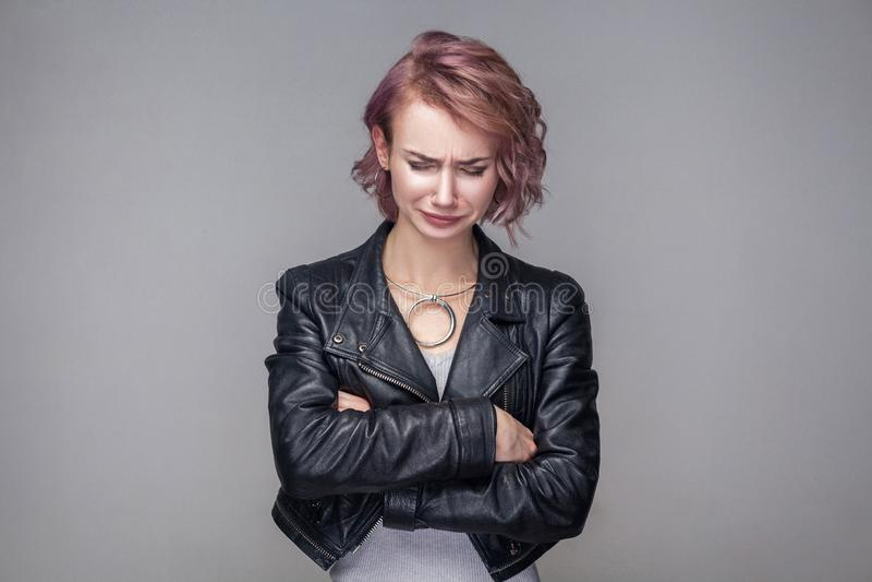 Portret die van gedeprimeerd mooi meisje met kort kapsel en make-up in het toevallige jasje die van het stijl zwarte leer, hoofd  stock foto