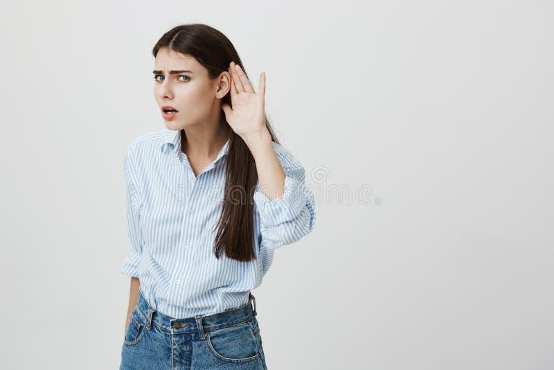 Portret die van geinteresseerde jonge vrouw met lang haar, overhemd en jeans dragen en hand houden dichtbij oor, die luisteren aa stock afbeeldingen